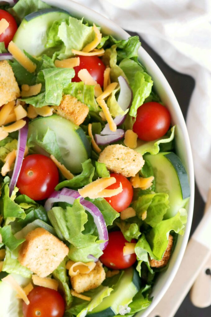 An overhead shot, close up shot of a House Salad in a bowl with a salad serve on the side and a napkin in the background.