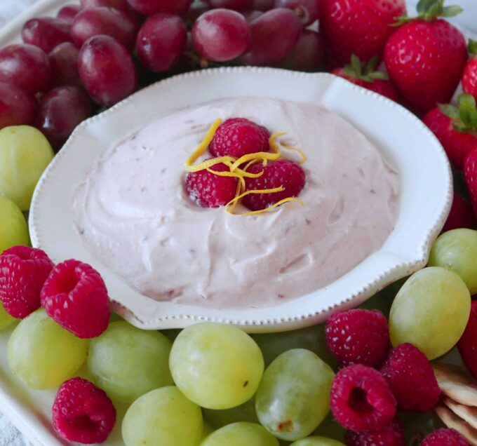 A close up shot of raspberry fruit dip in a white serving bowl surrounded by fresh green and red grapes, raspberries, and whole strawberries.