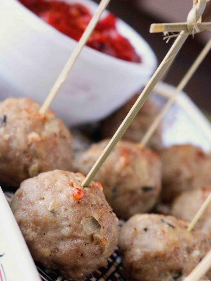 Several turkey meatballs on a serving dish with toothpicks stuck through them.  Off to the side is a small bowl of marinara.