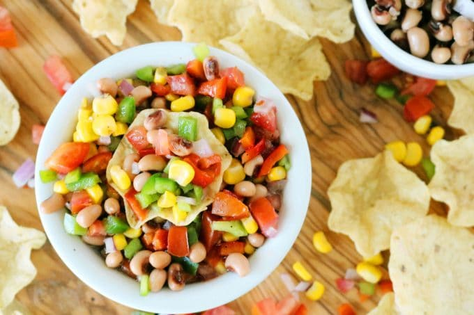 An overhead shot of Texas Caviar Dip served in a white bowl surrounded by Tortilla Chips.