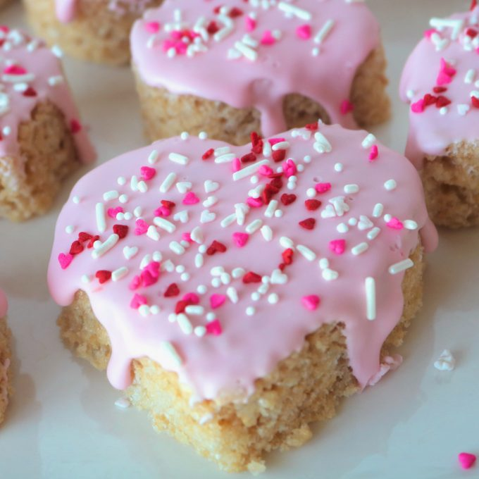 A close up shot of a heart shaped rice krispie treat that is dripping with light pink icing and sprinkled with red, white and pink sprinkles.