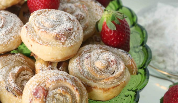 Puff pastry dessert clustered together with two whole strawberries placed between the pastries.