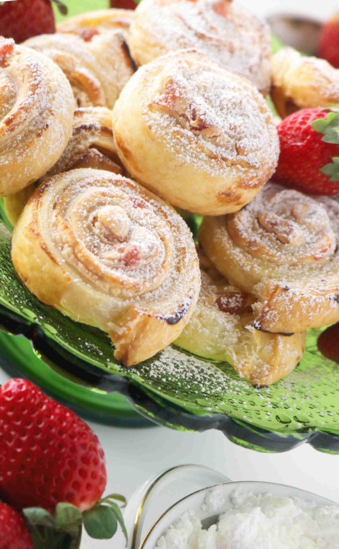 Puff pastry pinwheels stacked together on a green glass cake stand surrounded by fresh whole strawberries.