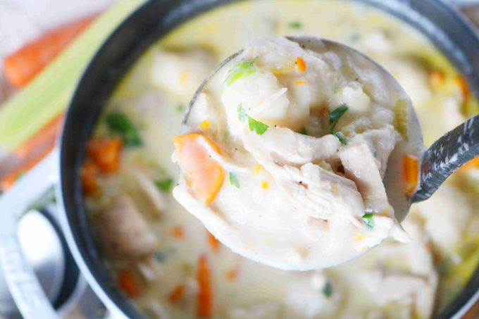 A close-up shot of a ladle-full of chicken and dumplings with a big pot of soup below.