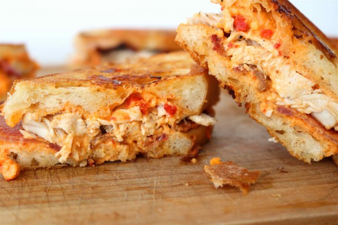 A grilled pimento cheese sandwiched that has been halved and stacked on top of each other.  The sandwiches are sitting on top of a wooden cutting board.
