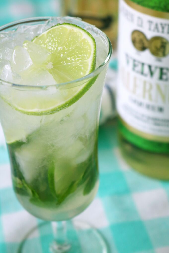 An overhead shot of a tall clear glass with a round slice of lime floating on top. At the bottom of the glass are mint leaves and more lime slices. In the background is a bottle of Falernum liqueur sitting on top of a teal and white checkered tablecloth.