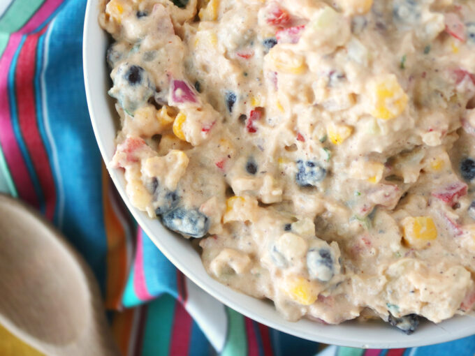 Southwestern Potato Salad Recipe in a white serving bowl sitting on top of a striped colorful napkin. Off to the left side lying flat is a wooden spoon.