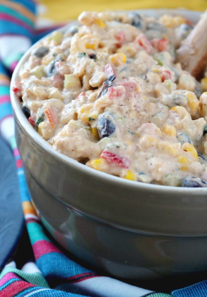Southwestern Potato Salad in a gray serving bowl sitting on top of a colorful striped napkin.