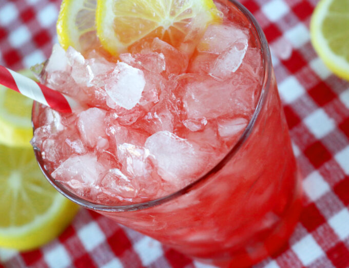 An overhead shot of a clear glass filled with ice, lemon slices, and a red and white striped straw.  In the background are lemon slices all sitting on top of a white and red checkered tablecloth.