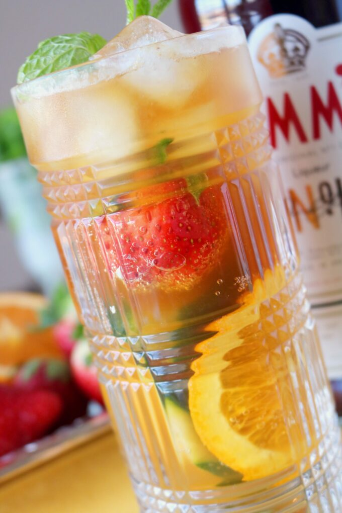 A close up shot a highball clear glass filled with ice, sliced oranges, strawberries and topped with fresh mint leaves.  In the background is a bottle of Pimms.