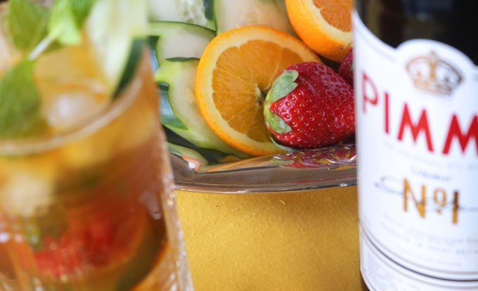 An overhead shot of a pimms cup cocktail, a bowl of sliced oranges, cucumber, and whole strawberries.  Off to the side is a bottle of pimms.