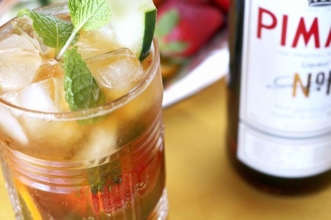 A close up shot of the cocktail with a bottle of pimms in the background.