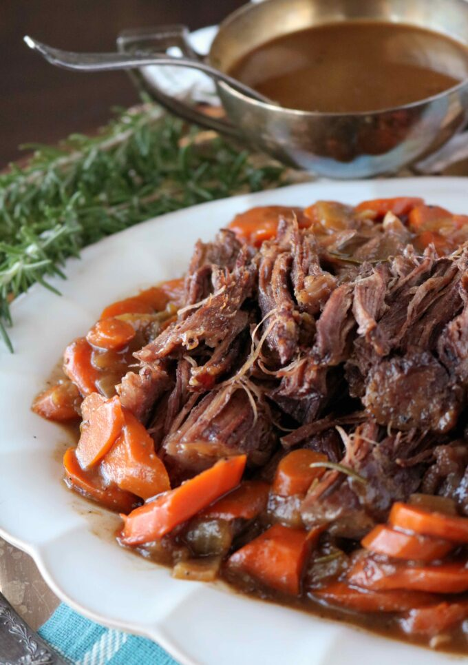 Shredded pot roast on a platter surrounded by carrots with a bowl of gravy in the background.