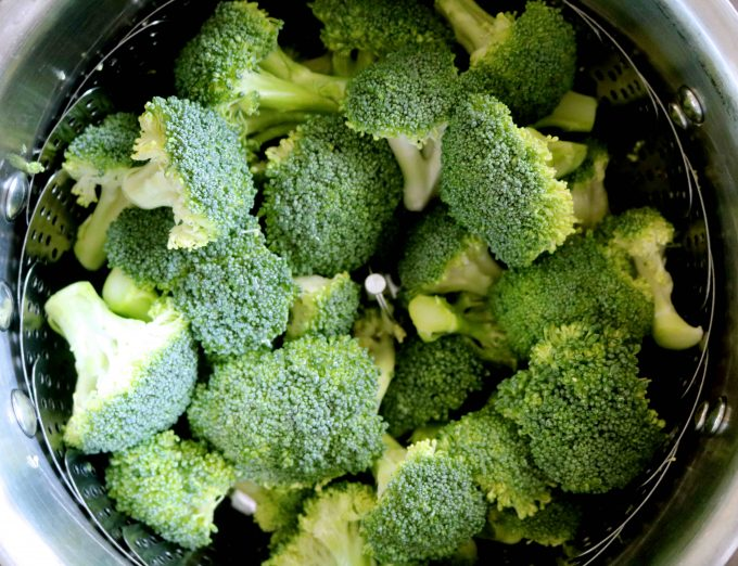 An overhead shot of raw broccoli in a steamer basket.