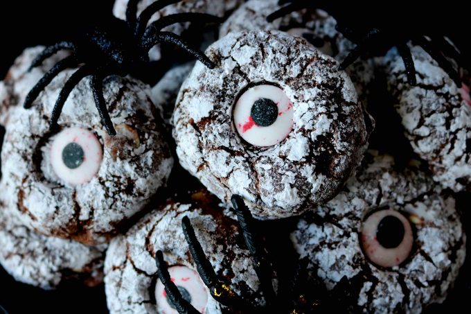 Chocolate crinkles cookies dusted with powdered sugar with piece of eye candy placed in the middle of the cookies.