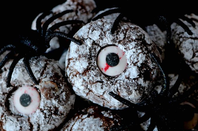 Chocolate crinkle cookies topped with powdered sugar and in the center is a piece of eye candy. Fake spiders are sitting on top of the cookies.