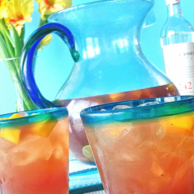 A glass pitcher and two cocktail glasses filled with sangria cocktail. The pitcher has a blue handle and in the background are yellow flowers in a clear vase and a bottle of rum.