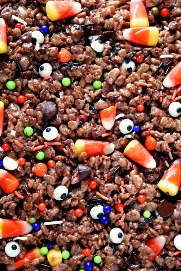A full image of chocolate rice krispies sprinkled with eye candy, candy corn, chocolate chips, and festive sprinkles.