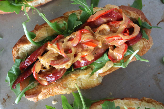 A sandwich featuring kielbasa sausage, savory sauteed peppers, spicy arugula and a tangy mustard sauce.