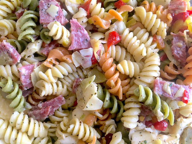 A close up shot of tri-color Rotini, thinly diced salami and roasted red peppers.