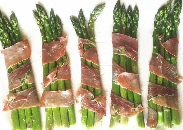 A beautifully presented side dish featuring quick-roasted asparagus wrapped with prosciutto.