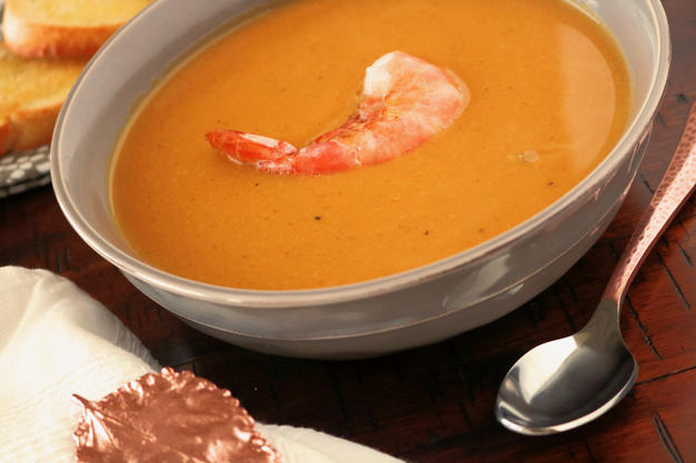 A bowl of butternut squash soup with  one single shrimp centered in the bowl.  To the right side of the bowl lying flat is a silver spoon.