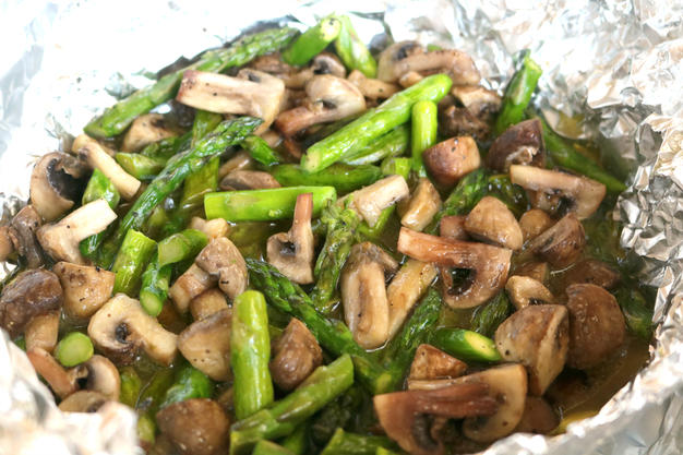 Cooked asparagus and mushrooms in a pocket of aluminum foil.