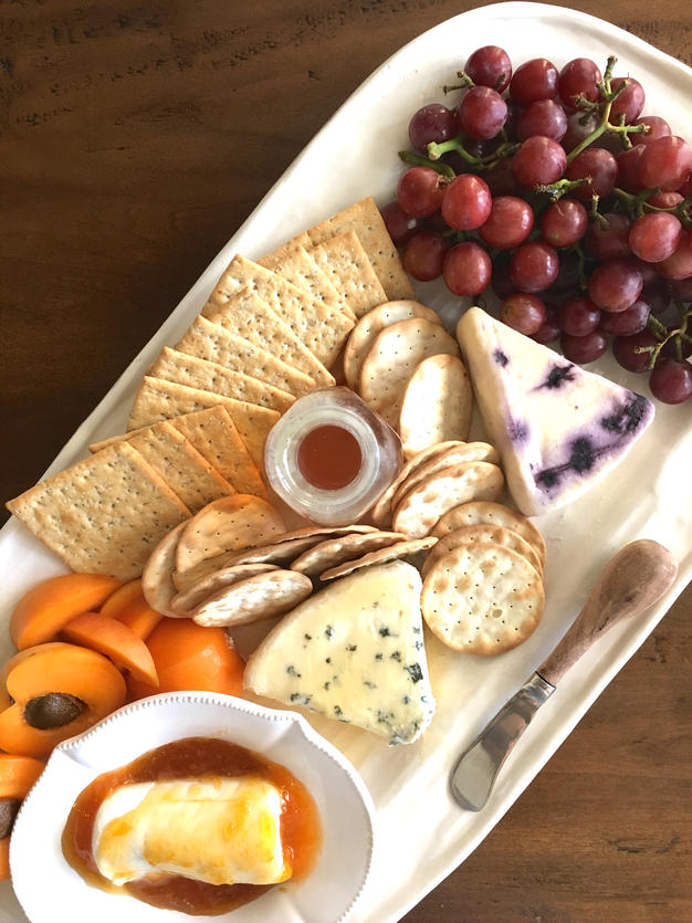 A white serving platter topped with apricots, blue cheese, a jar of honey, bundle of grapes and an assortment of crackers.