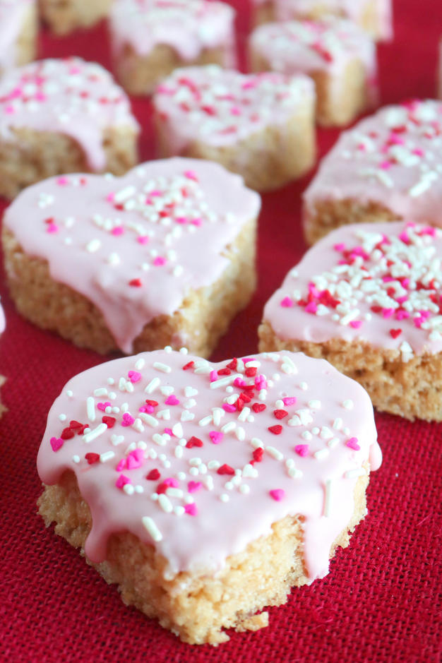 Heart shaped rice krispie treats sitting on top of a red tablecloth.  Light pink icing is dripping over the sides of each heart and topped with red, white and pink sprinkles.