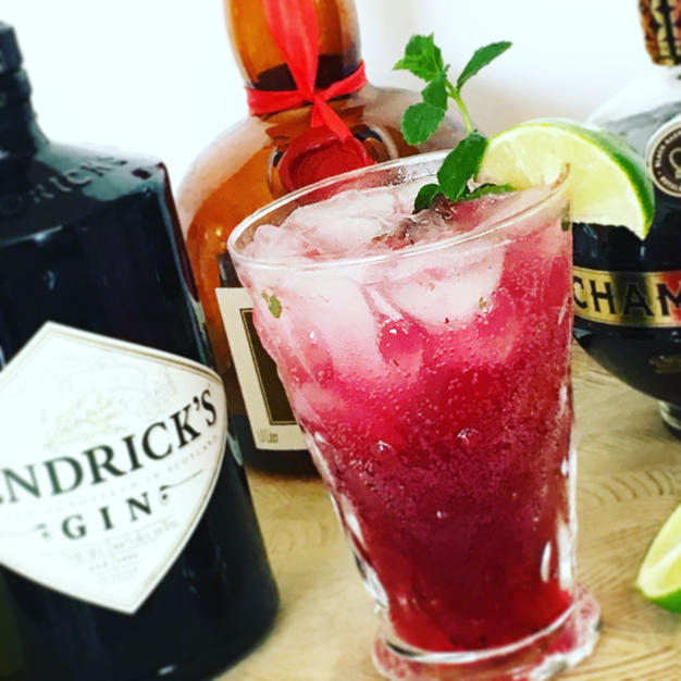 A bottle of hendricks gin, grand marnier, and chambord all placed behind the blueberry cocktail.  The cocktail has a sprig of mint coming out of the top and a lime wedge sitting on the edge of the glass.