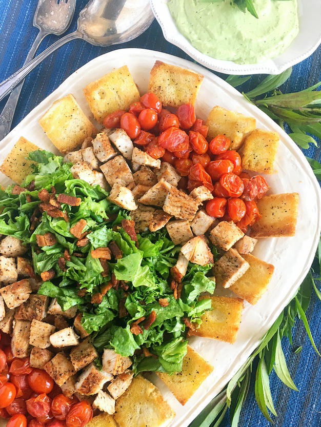 A salad layered on a white serving dish.  The salad is layered in this order, roasted tomatoes, turkey, lettuce with homemade croutons surrounding the salad.  Off to the side is a bowl of dressing, sprigs of herbs and two silver serving spoons.
