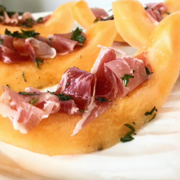 Slices of cantaloupe with thinly sliced proscuitto in the center of the cantaloupe.  The cantaloupe slices are sprinkled with basil and sitting on a white serving dish.