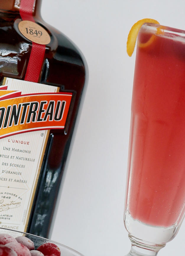 A bottle of orange liqueur and a tall clear glass of a raspberry mimosa with a sliver of orange rind sitting on the edge of the glass.