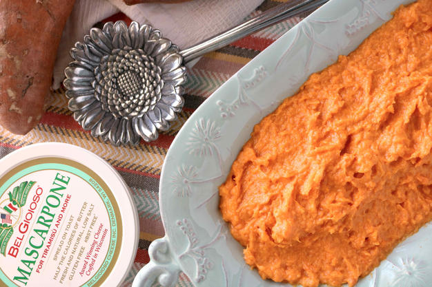 A light blue serving dish full of mashed sweet potatoes.  Off to the the side is a container of mascarpone cheese and a silver flower serving spoon.