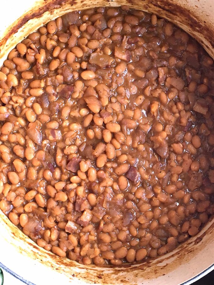 A close up shot of beans being cooked in a dutch oven.