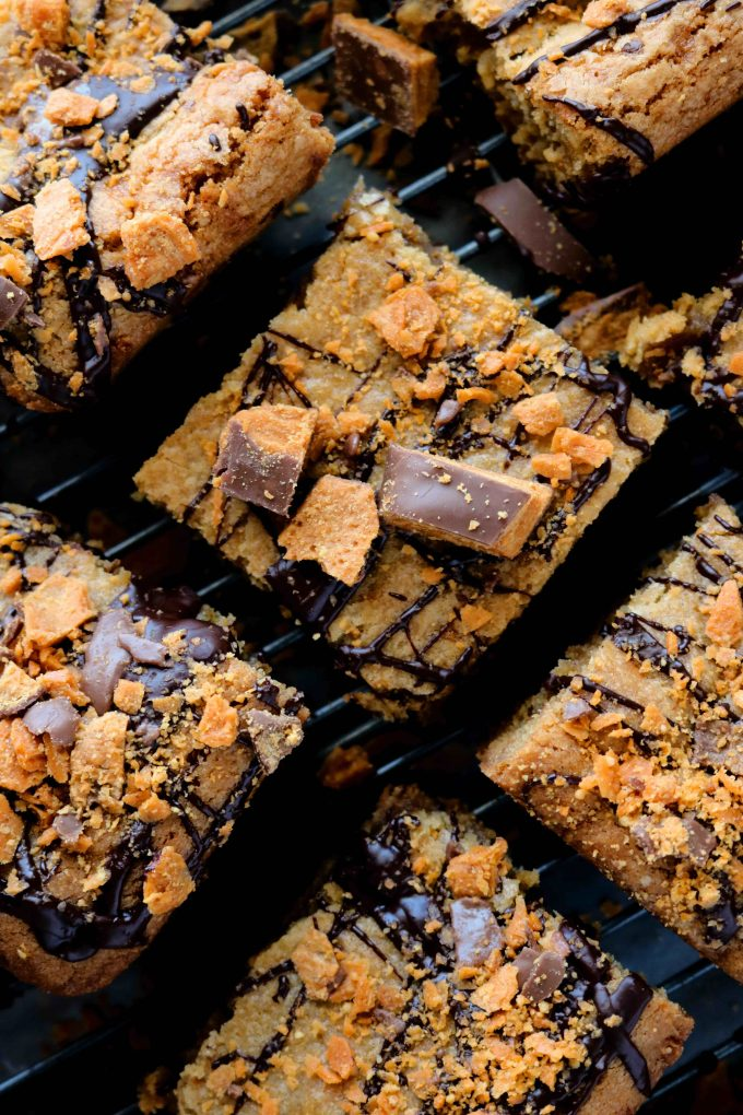 Square halloween Blondies topped with butterfinger candy and drizzled chocolate all sitting on a black cooling rack.