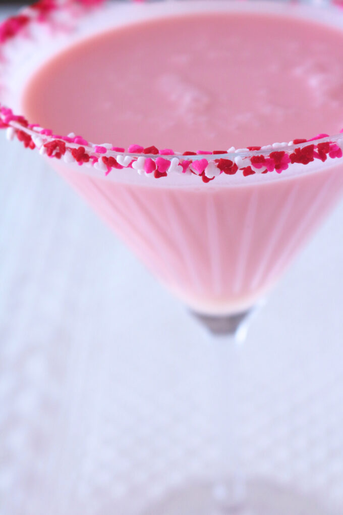 A close up shot of a martini glass full of a cherry cheesecake cocktail rimmed with red, white and pink heart sprinkles.