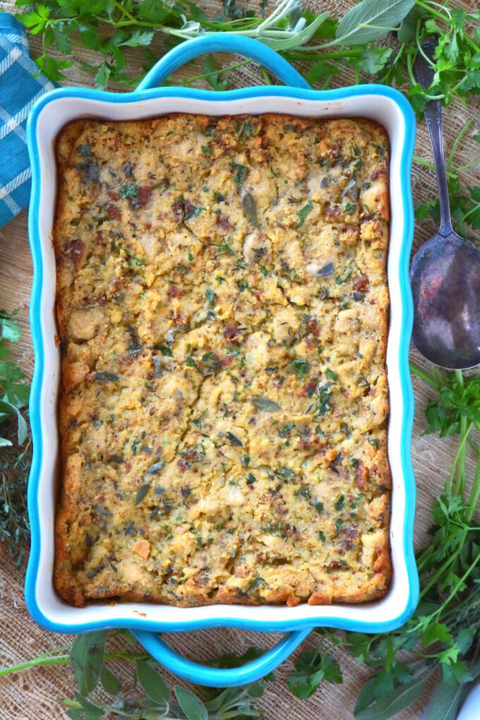 An overhead shot of southern cornbread dressing in a teal scalloped baking dish with handles.  The dish is surrounded by fresh herbs.