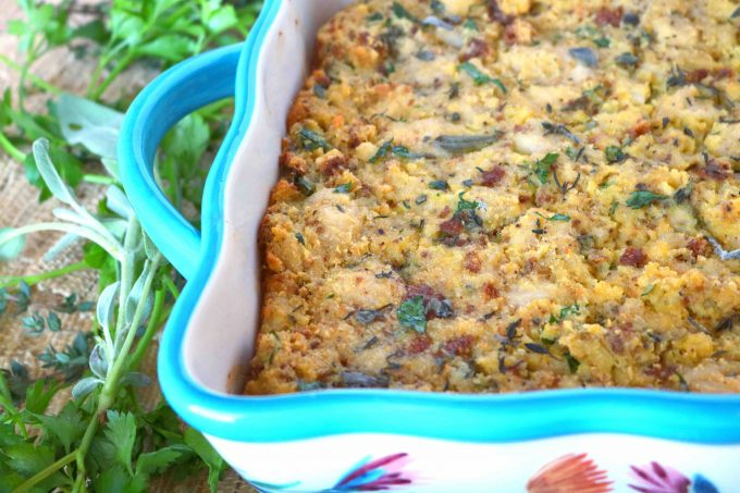 A close up shot of the left corner of the southern cornbread dressing in a teal and white decorative baking dish. Lying flat next to the dish are fresh herbs.