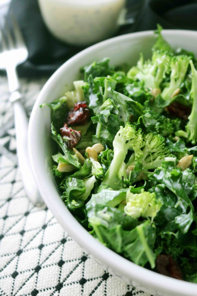 A white bowl full of torn kale leaves, broccoli florets, dried cranberries, and pine nuts.  The bowl is sitting on top of a white and black patterned placemat with a silver fork lying flat in the background.