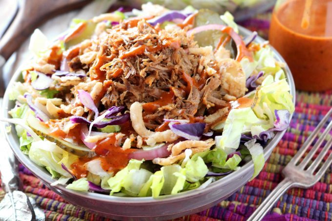 A gray bowl full of shredded lettuce, cabbage, french fried onions, and a tangy barbecue dressing. The bowl is sitting on top of a colorful placemat with a fork lying flat next to the bowl.