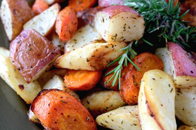 A roasted root vegetable medley, featuring parsnips, carrots, and red potatoes, sprinkled with fresh minced rosemary.