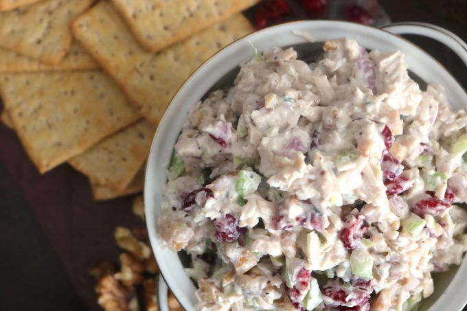 An overhead up shot of turkey salad in a white bowl with several crackers off to the side.