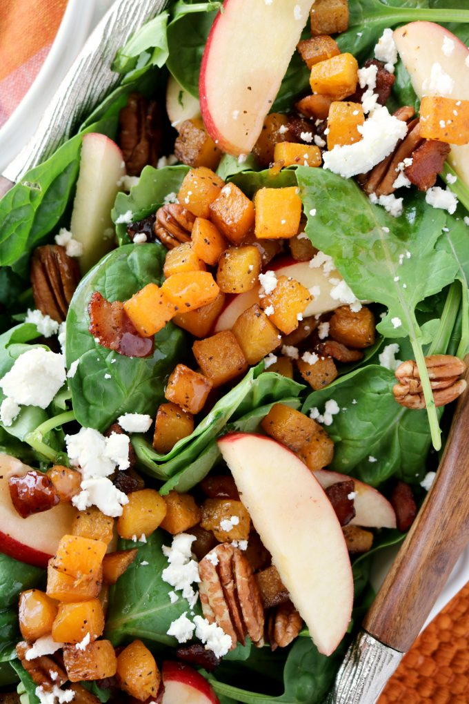 An overhead shot of roasted butternut squash salad with crumbled goat cheese, pecans, a pieces of bacon.