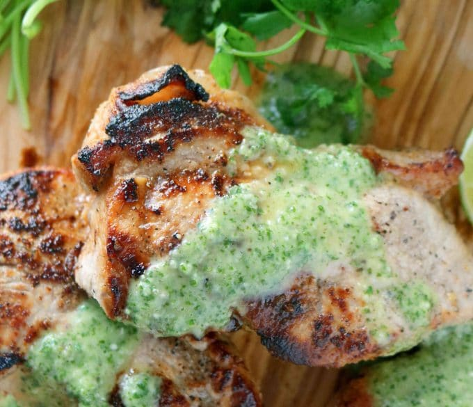 An overhead shot of pork chops drizzled with chimichurri sauce.  The pork chops are resting on a wood platter.