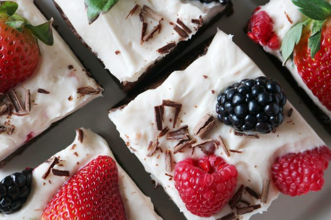 A close up shot of homemade brownies squares topped with strawberry cream cheese icing. On top of each square are chocolate shavings, whole blackberries, raspberries, and strawberries.
