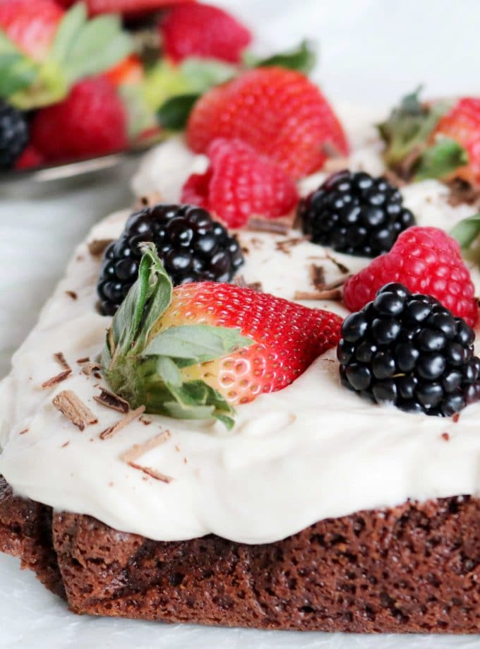 Whole fresh assorted berries top these homemade brownies with strawberry cream cheese frosting.