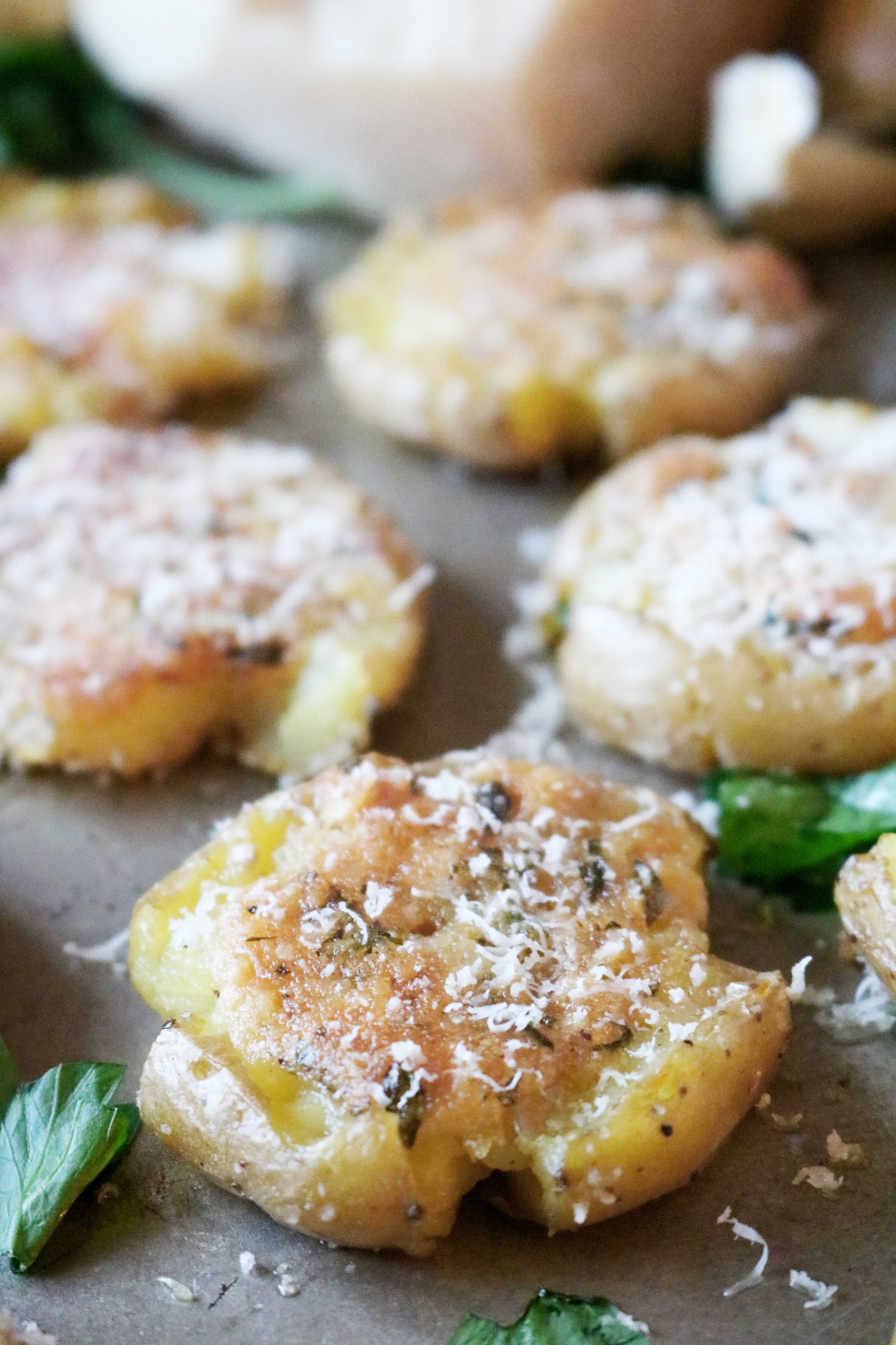 A smashed potatoes recipe featuring baby gold potatoes (or red potatoes) smashed and smeared with a garlic-Parmesan butter, then roasted to crispy perfection. #potatorecipes #vegetablesidedishes #smashedpotatoes #roastedpotatoes #potatosidedish #easysidedish #crowdpleaser