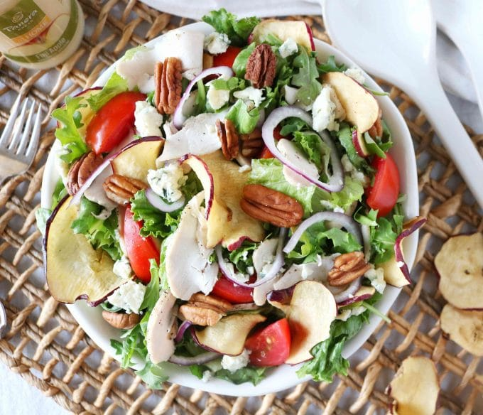 An overhead shot of a copycat Panera salad with dried apples, chicken, tomatoes, and lettuce mixed together in a bowl.