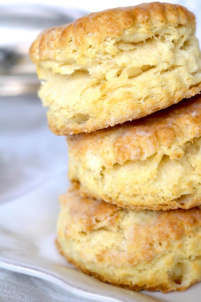 Three homemade southern biscuits that are stacked on top of each other.